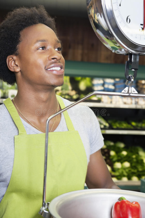 African American male store clerk weighing bell pepper royalty free stock image