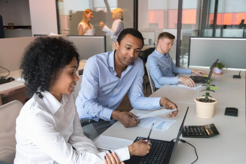 Black male supervisor analyze female trainee work at workplace. African American male supervisor test black millennial female intern check skills at laptop at royalty free stock image