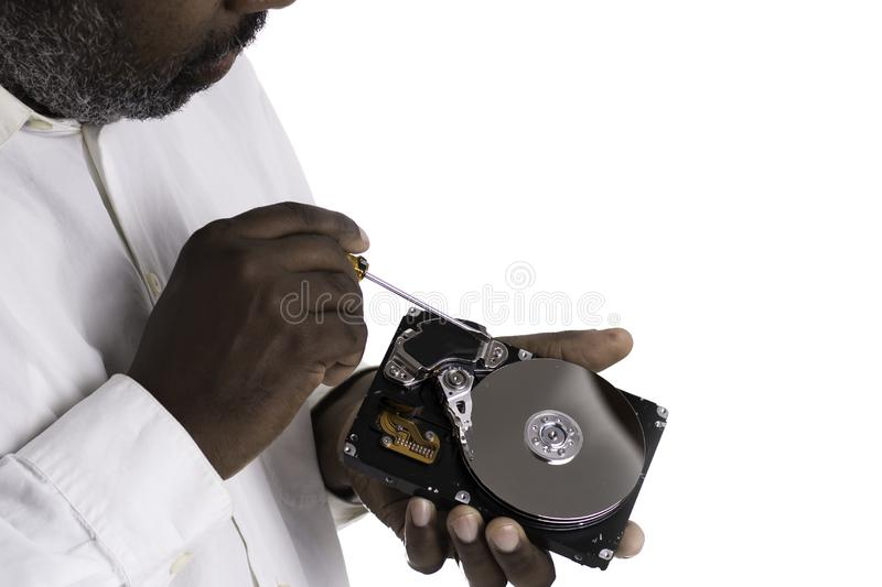 African American Male technician hand holding and working on  computer hard drive with screwdriver royalty free stock photo