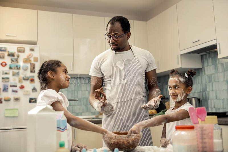 African-American man in apron cooking chocolate pie with daughters. Cook with daughters. African-American men wearing striped apron cooking chocolate pie with royalty free stock image