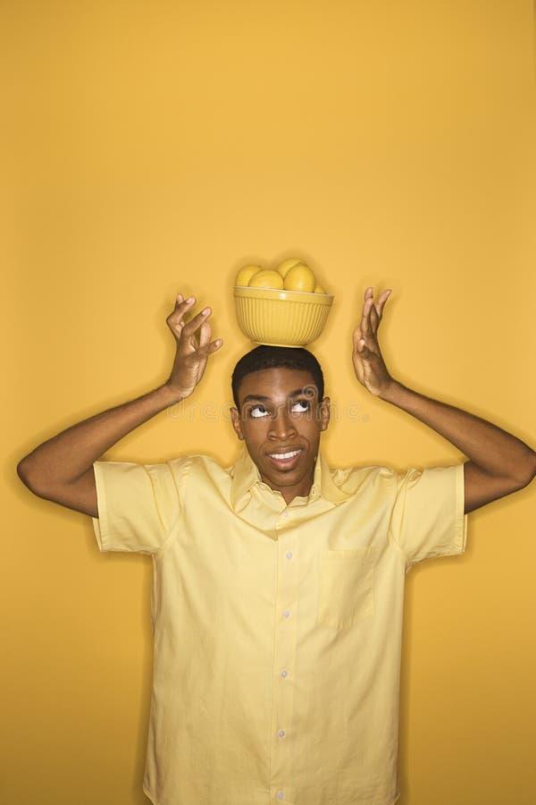 Free African-American Man Balancing Bowl Of Lemons On His Head. Stock Photos - 2043873
