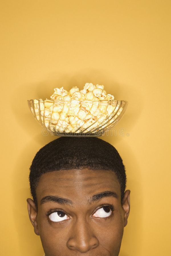 African-American man balancing bowl of popcorn on head. Young African-American man balancing bowl of popcorn on his head on yellow background stock photos