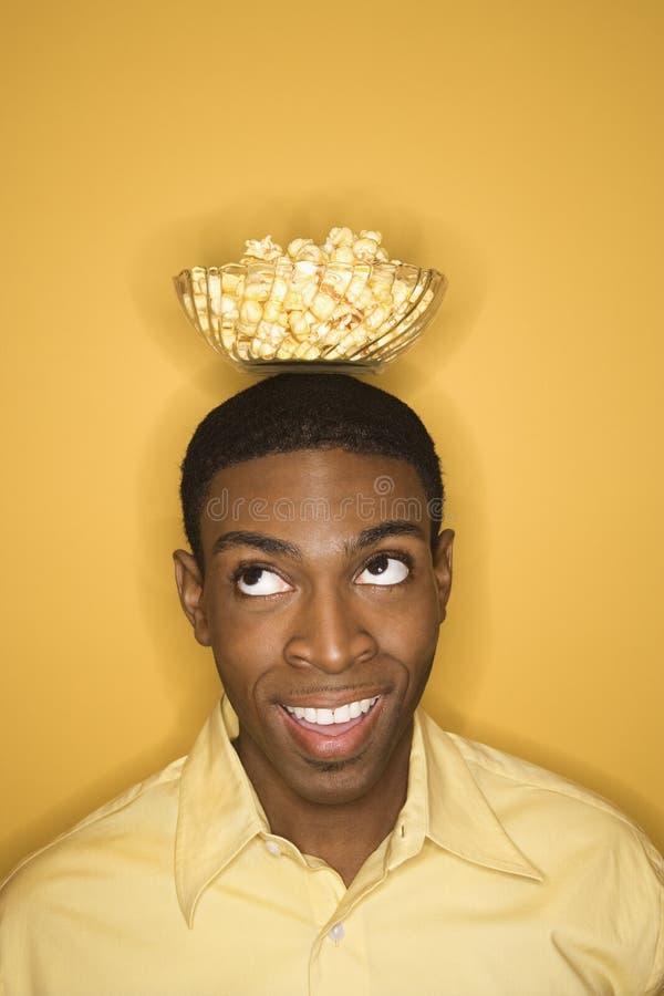 African-American man balancing bowl of popcorn on head. Young African-American man balancing bowl of popcorn on his head on yellow background royalty free stock photo