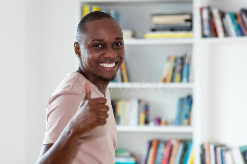 African american man with bald head showing thumb up stock photo