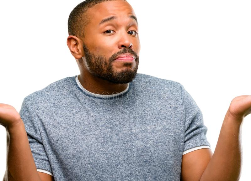 African young man isolated over white background. African american man with beard doubt expression, confuse and wonder concept, uncertain future shrugging royalty free stock photos