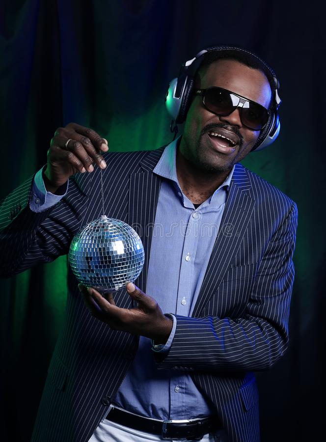 African American man Disco Ball Over Black Background. African-American man in black suits and sunglasses standing near disco ball stock image