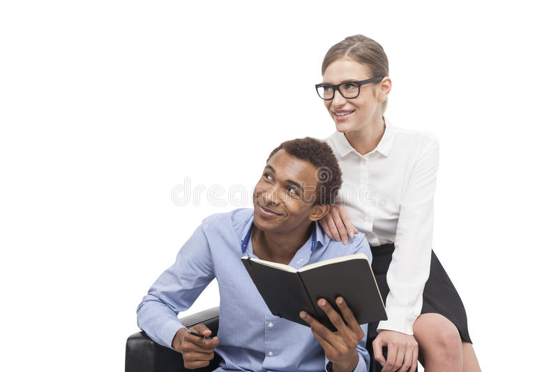 African American man and blond woman in armchair stock images