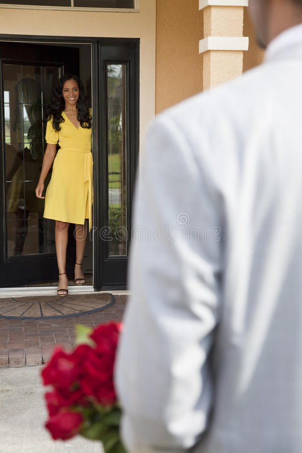 African American Man Bringing Flowers to Wife stock image