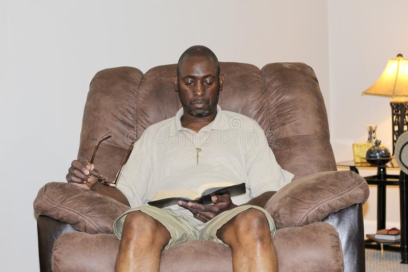 African-American man in a chair and reading the Bible royalty free stock photos