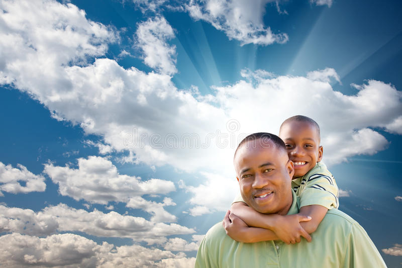 African American Man With Child Over Sky Stock Photo