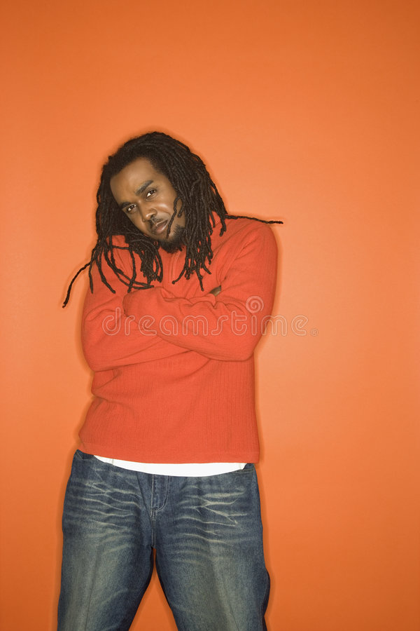 African-American man with crossed arms wearing orange clothing. African-American mid-adult man with crossed arms and attitude wearing orange clothing on orange stock photography