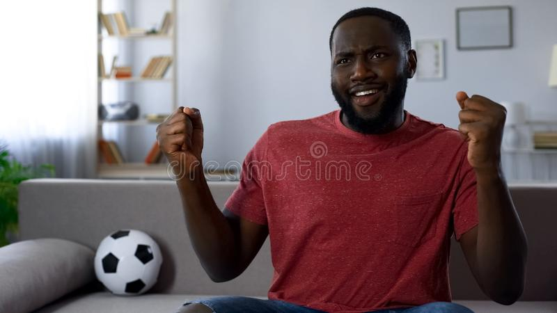 African-american man dancing victoriously, celebrating victory of football team royalty free stock image