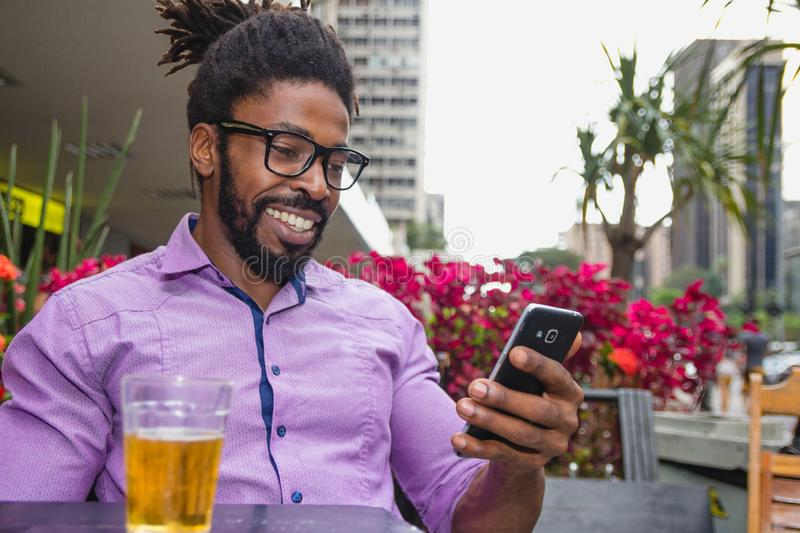 African american man drinking beer and using cell phone royalty free stock photos
