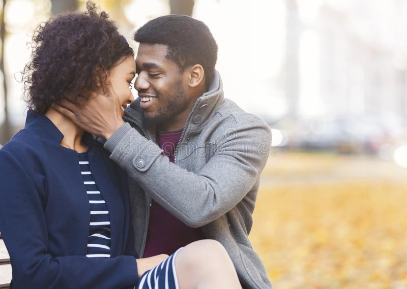 African american man embracing his woman, saying sweet words stock images