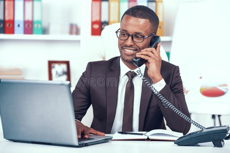 African American Man Has Business Call in Office. royalty free stock image