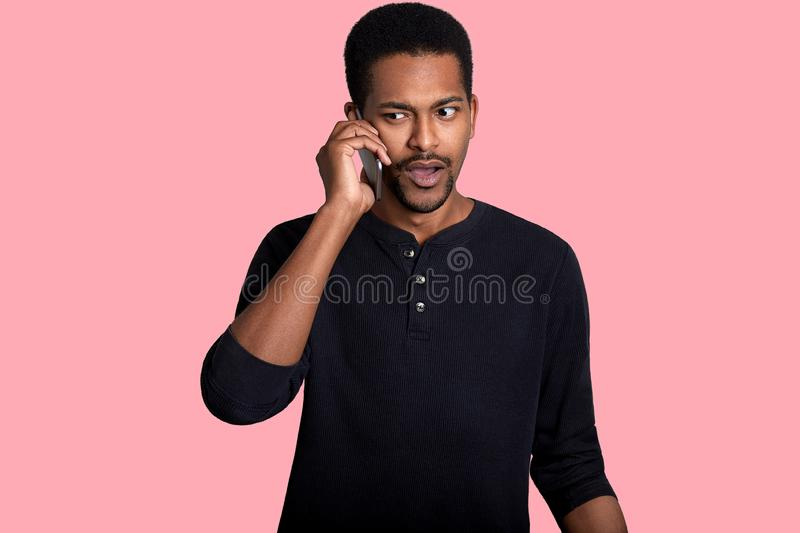 African American man has telephone coversation, hears something unpleasant news, looks aside, wears black outfit. Handsome dark royalty free stock photo