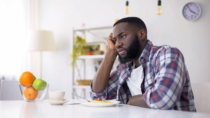 African-American man having no appetite, eating disorder, depression problem royalty free stock photos