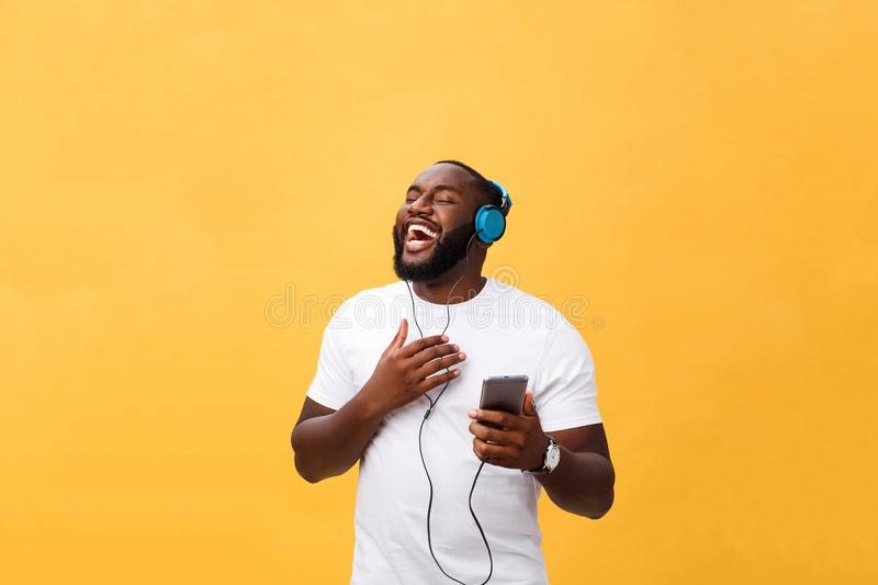 African American man with headphones listen and dance with music. Isolated on yellow background royalty free stock photo