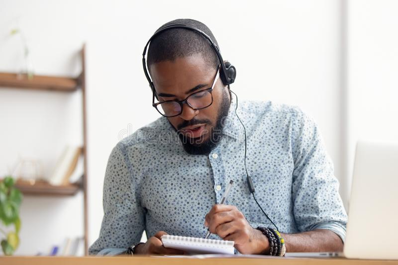 African American man in headphones taking E-learning course at office. African American man in headphones sitting at office table taking course of E-learning stock image