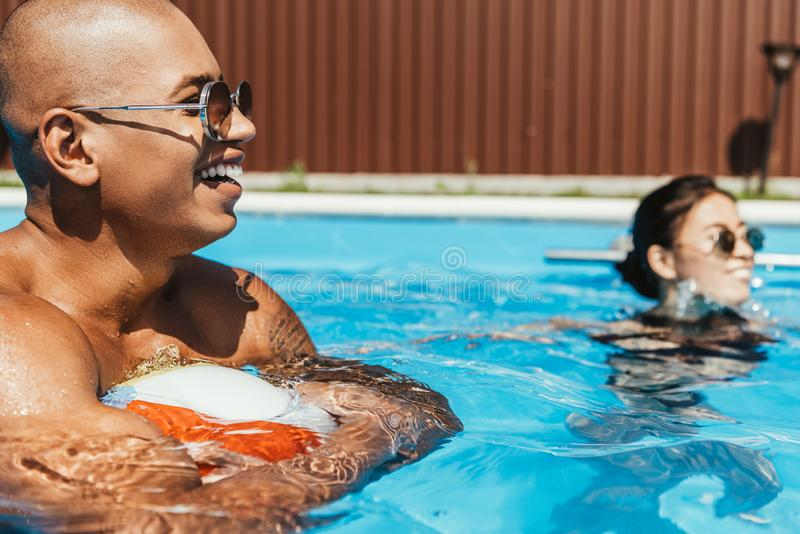 african american man holding beach ball in swimming pool with girlfriend stock images