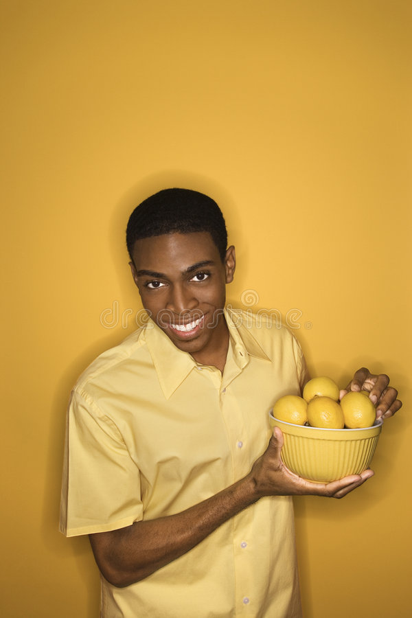 Free African-American Man Holding Bowl Of Lemons. Stock Image - 2043871