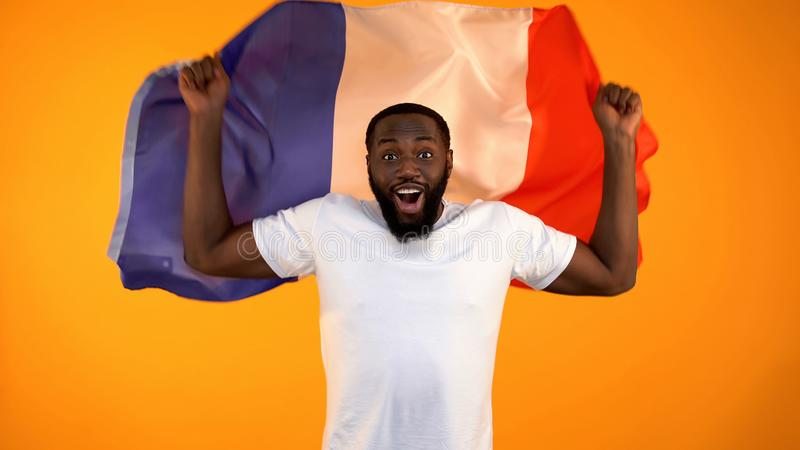 African-American man holding French flag, football fan supporting national team stock photos