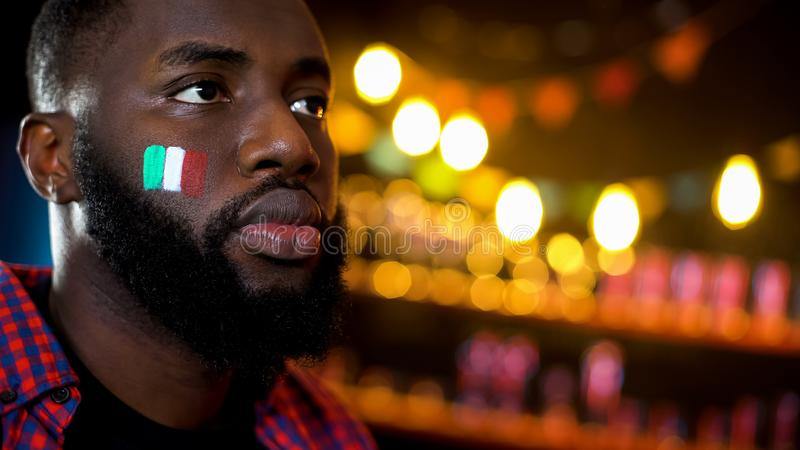 African-american man with italian flag on cheek attentively watching concert. Stock photo stock images
