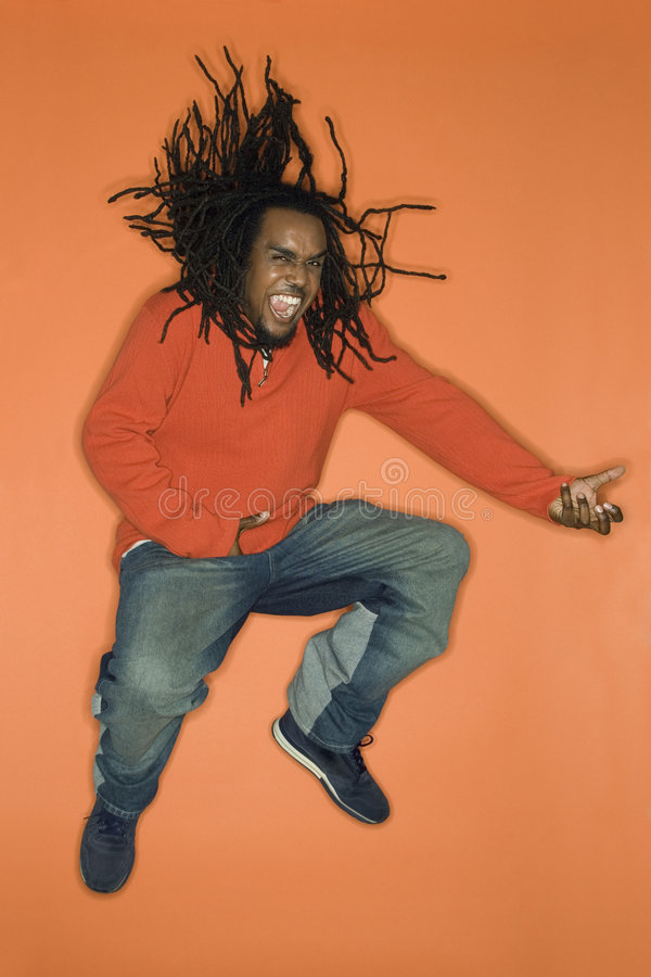 African-American man jumping and playing air guitar. royalty free stock photos