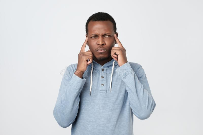 African american man keeps fingers on temples selects best suitable solution stock photography