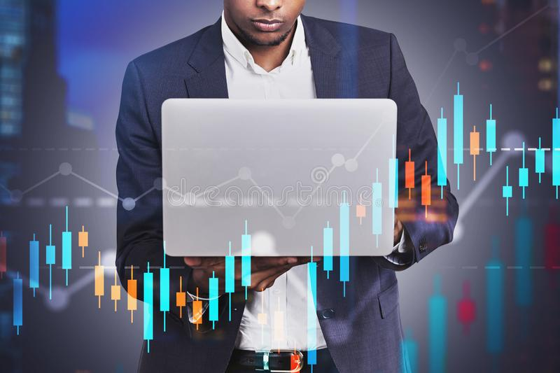 African American man with laptop, graph. Serious young African American businessman working with laptop in blurred night city with double exposure of graphs royalty free stock photography