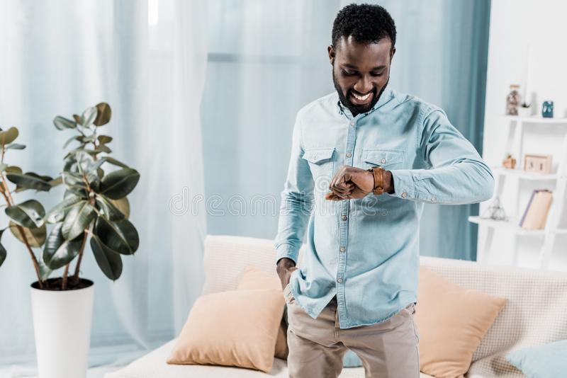 African american man looking down at watch on wrist in. Living room royalty free stock photography