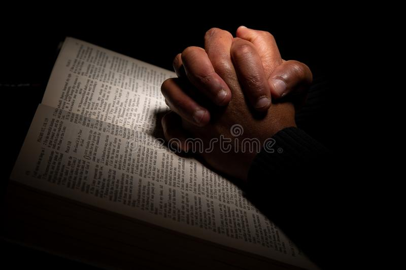 African American Man Praying with Hands on Top of the Bible royalty free stock photography