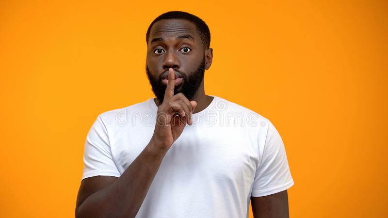 African-American man showing silence gesture, keeping secret, yellow background stock photos