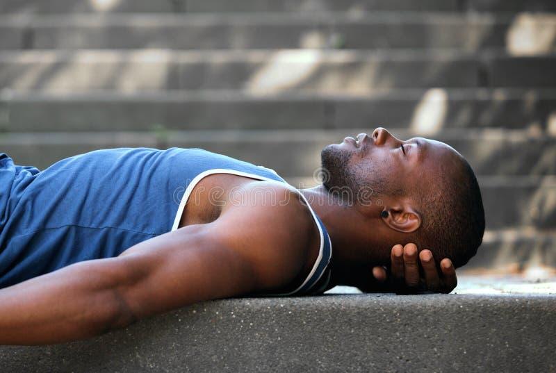 African american man sleeping outside stock photo