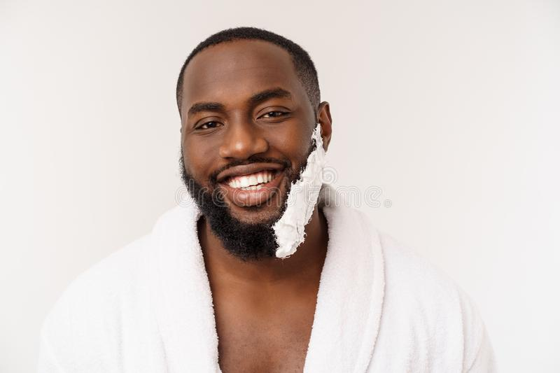 African American man smears shaving cream on face by shaving brush. Male hygiene. Isolated on white background. Studio stock photography