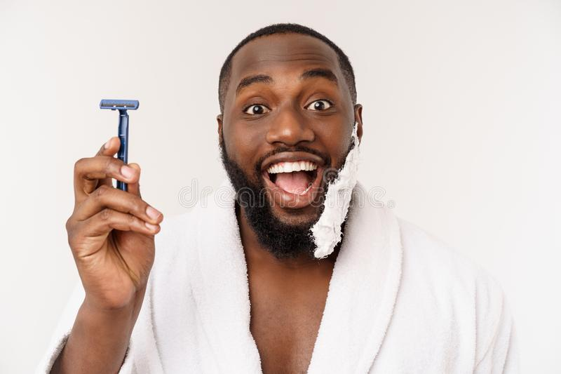 African American man smears shaving cream on face by shaving brush. Male hygiene. Isolated on white background. Studio stock photos