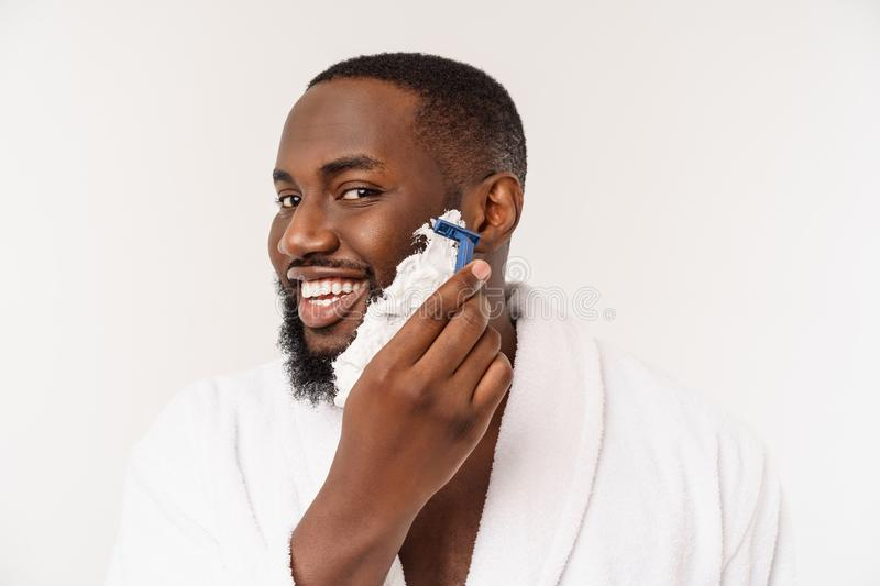 African American man smears shaving cream on face by shaving brush. Male hygiene. Isolated on white background. Studio stock images
