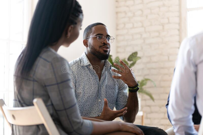 African American man speak at group therapy session. Excited african American men in glasses sit in circle at team therapy session talking sharing thoughts or royalty free stock photos