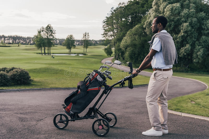 African american man in sunglasses walking with bag full of golf clubs. Smiling african american man in sunglasses walking with bag full of golf clubs stock image