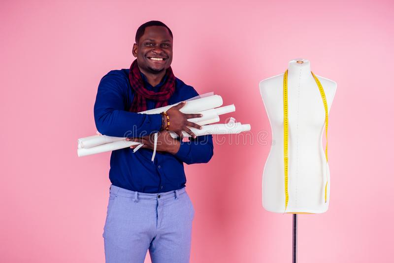African American man tailor seamstress workshop stylish male model clothes designer posing next to the mannequin on pink. African American man tailor seamstress royalty free stock images