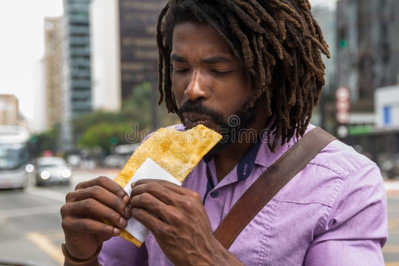 African american man tasting brazilian snack known as Pastel - asian recipe stock images