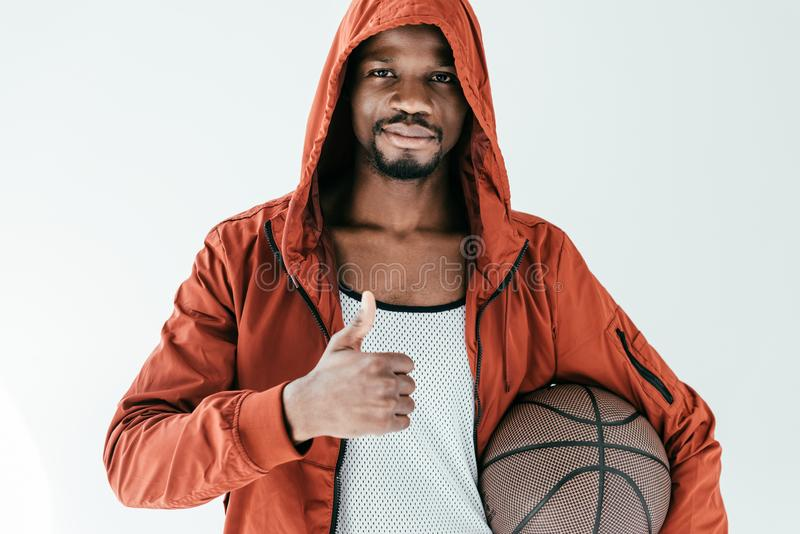 African american man with thumb up holding basketball ball. Isolated on white royalty free stock photos