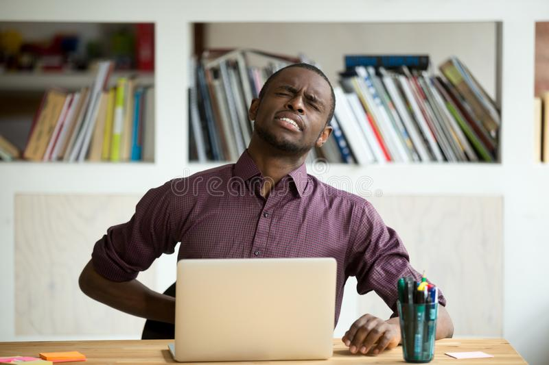 African-american man touching back sitting at desk feeling sudde. N backache, black businessman suffering from low-back lumbar pain after sedentary work at stock images