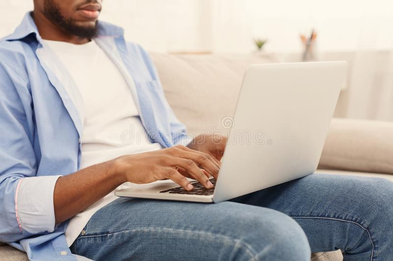 African-american man typing on his laptop at home. Typing new blog post. African-american man blogger using his laptop, sitting on couch at home, copy space stock image
