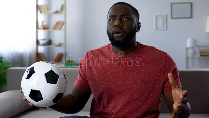 African-american man watching football game at home, unhappy with match score. Stock photo stock photo
