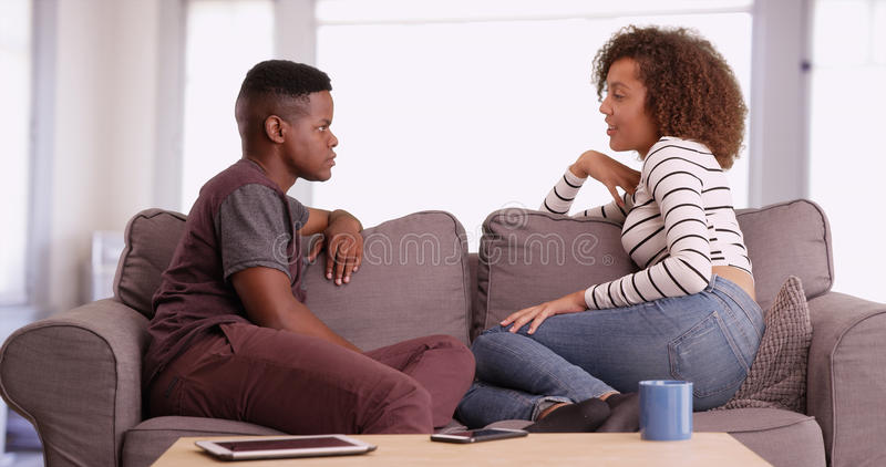 African American man and woman talk while relaxing on their couch in their living room. African American men and women talk while relaxing on their couch in royalty free stock images