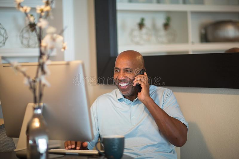 Mature African American man working from his home office. African American man working from his home office stock photo