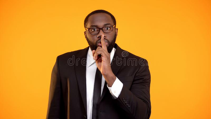 African-american manager showing quiet sign, gossips, personal data disclosure stock photo