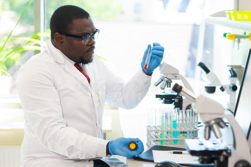 African-american medical doctor working in research lab. Science assistant making pharmaceutical experiments. Chemistry. African-american Medical doctor working stock photos
