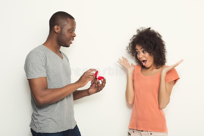 Black man proposing to his shocked girlfriend stock photography